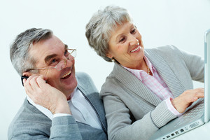Portrait of mature woman using laptop and her husband calling on cellphone