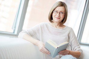 Portrait of mature woman with book looking at camera