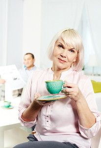 Portrait of mature woman with cup looking at camera on background of her husband