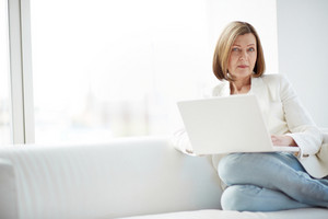 Portrait of mature woman with laptop sitting on sofa and looking at camera