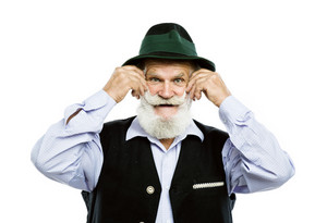 Portrait of old bearded bavarian man in traditional felt hat, posing in studio on white background