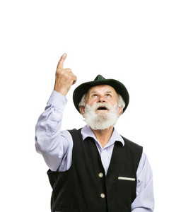 Portrait of old bearded bavarian man in traditional hat looking and pointing upwards isolated on white background