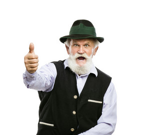 Portrait of old bearded bavarian man in traditional hat with thumbs up isolated on white background