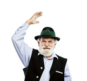 Portrait of old bearded bavarian man raising his hat in a greeting sign in studio on white background