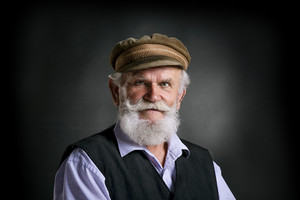 Portrait of old bearded man in traditional cap, posing in studio on black background
