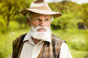 Portrait of old farmer with beard and hat in his backyard