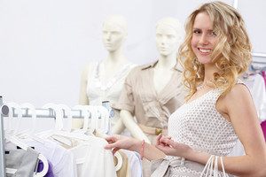 Portrait of pretty blonde choosing new tanktop and looking at camera in clothing department