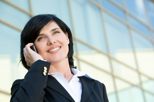 Portrait of pretty business leader talking by mobile phone with smile