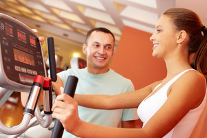 Portrait of pretty girl training in gym with her trainer near by