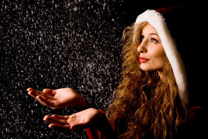 Portrait of pretty girl with open palms catching falling snow over dark background