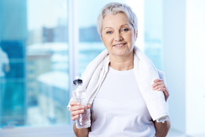 Portrait of pretty senior woman with bottle of water in gym
