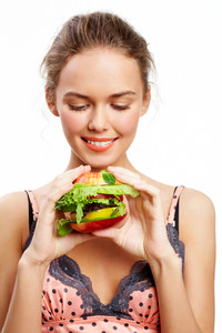 Portrait of pretty young girl looking at vegetable burger in her hands