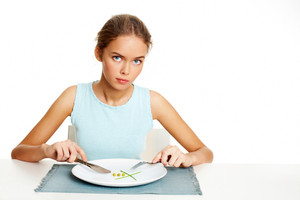 Portrait of pretty young girl ready to eat peas and leeks