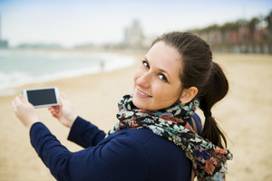 Portrait of pretty young traveler taking picture with cell phone on the beach on a cold day.