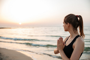 Portrait of relaxed woman meditating outdoors at the beach