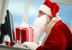 Portrait of Santa Claus in front of computer monitor with gifts