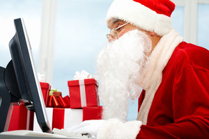Portrait of Santa Claus in front of computer monitor