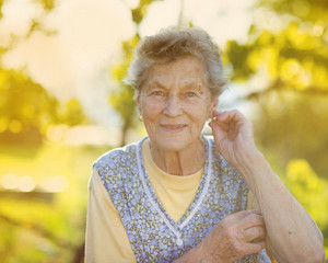 Portrait of senior woman in apron in the sunny garden