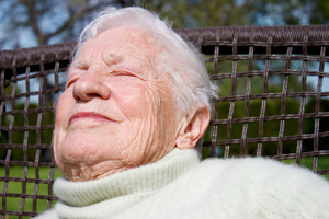 Portrait of senior woman relaxing outside on garden chair