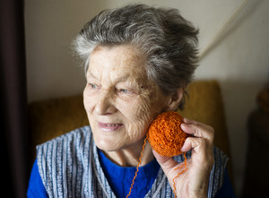 Portrait of senior woman sitting in armchair and knitting at home