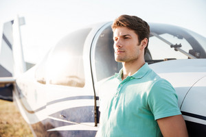 Portrait of serious attractive young man near small airplane