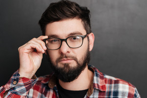 Portrait of serious bearded man touching glasses standing over chalkboard. Look at camera.
