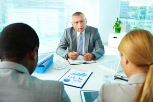 Portrait of serious boss interacting with his employees