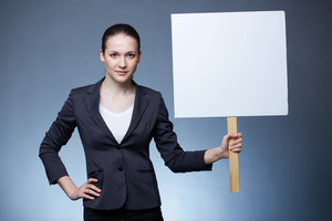 Portrait of serious businesswoman holding blank card in isolation