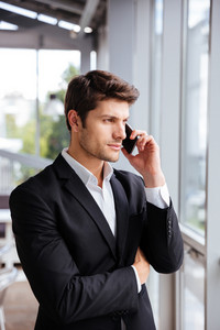 Portrait of serious young businessman talking on cell phone in office