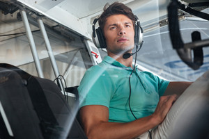Portrait of serious young man pilot in cabin of private aircraft
