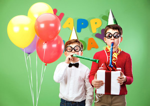 Portrait of smart boys in funny eyeglasses blowing into childish toys