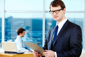 Portrait of smart businessman holding with glasses in working environment