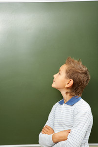 Portrait of smart lad looking at blackboard