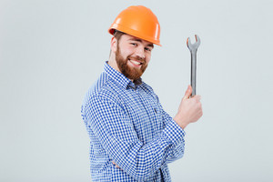 Portrait of smiling bearded young man in helmet with wrench over white background