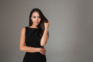 Portrait of smiling beautiful woman in black dress looking away isolated on a gray background