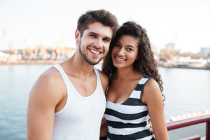 Portrait of smiling beautiful young couple standing near the sea