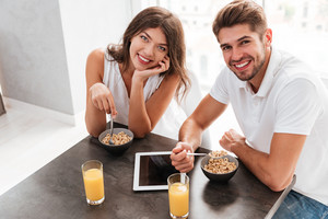Portrait of smiling beautiful young couple with blank screen tablet sitting and having breakfast on the kitchen
