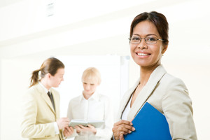 Portrait of smiling employer looking at camera with communicating associates at background