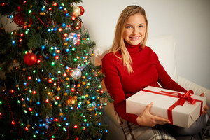 Portrait of smiling girl with big giftbox looking at camera with decorated xmas tree near by