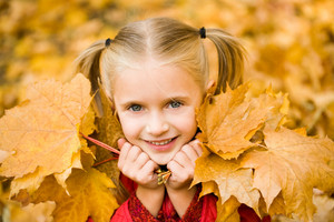Portrait of smiling girl with dry maple leaves looking at camera