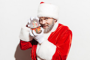 Portrait of smiling man santa claus playing with snow globe