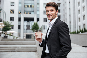 Portrait of smiling young businessman drinking coffee near business center