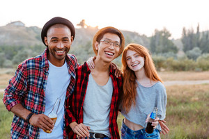 Portrait of smiling young people standing and hugging together outdoors