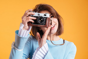 Portrait of smiling young woman taking photos with old vintage camera over yellow background