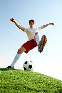 Portrait of soccer player before kicking ball on football field