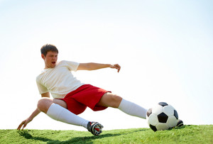 Portrait of soccer player kicking ball during game