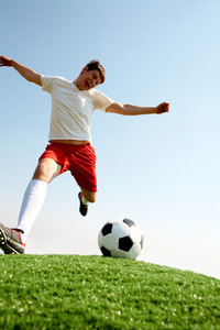 Portrait of soccer player kicking ball on football field