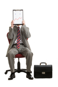 Portrait of stressed businessman sitting on armchair hiding his face with paper showing bad mood or confusion