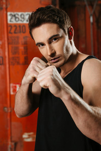 Portrait of strong boxer standing in a gym and posing with hands. Looking at camera.