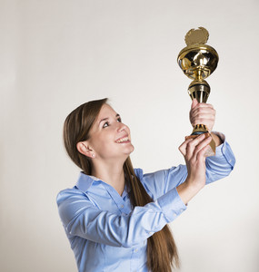 Portrait of successful business woman with trophy.
